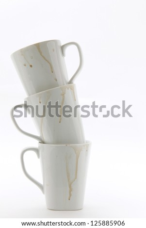 Stack of three used white coffee mugs on white - stock photo