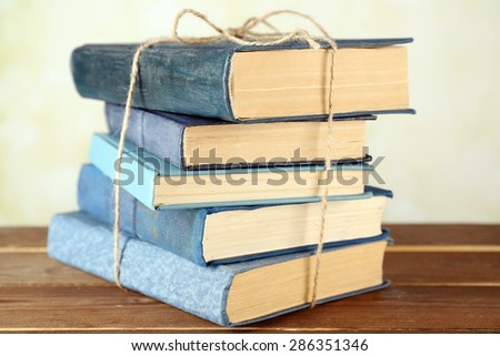 Stack of tied books on wooden table, closeup - stock photo
