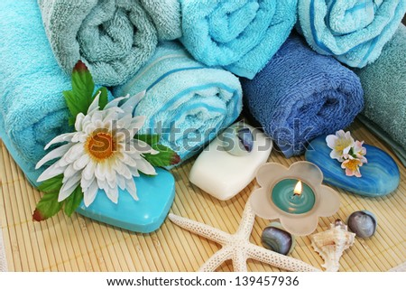 Stack of towels, candles, stones, flowers on mat background. - stock photo