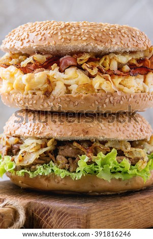 Stack of Two Bagels with stew beef, fresh salad, bacon, scrambled eggs and fried onion served on small wooden chopping board over white wooden table. Close up - stock photo