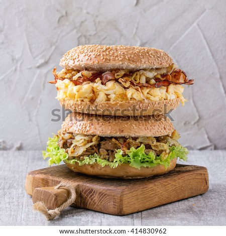Stack of Two Bagels with stew beef, fresh salad, bacon, scrambled eggs and fried onion served on small wooden chopping board over white wooden table. Square image - stock photo