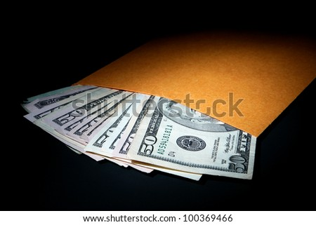 Stack of used large denomination US dollar bills sticking out of a plain manila brown envelope as a metaphor for under the table cash bribery and illegal hush money corruption in dramatic light - stock photo