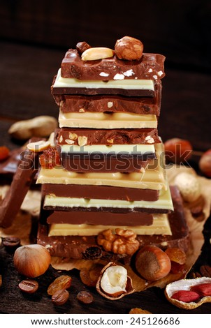 stack of various chocolate bars with nuts,raisins and coffee beans on dark wooden background - stock photo