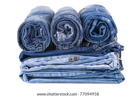 stack of various shades of blue jeans over white background - stock photo