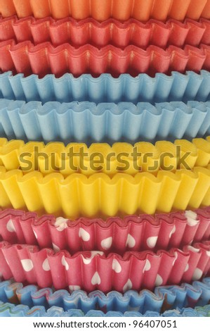 Stack of Vibrant Cupcake Wrappers Close Up Background. - stock photo