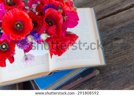 stack of vintage old books  on table with field flowers - stock photo