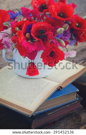 stack of vintage old books  on table with fresh field flowers, retro toned - stock photo