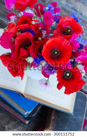 stack of vintage old books  on table with pot of  field flowers - stock photo