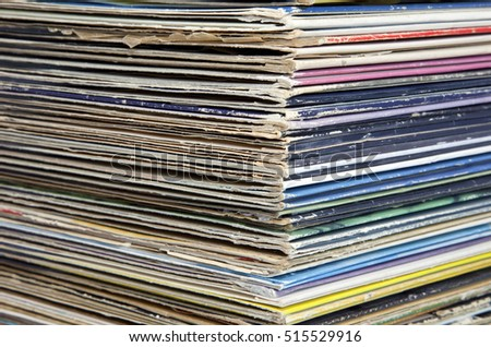 Stack of vinyl vintage lp records in worn sleeves.From and side view. Horizontal.