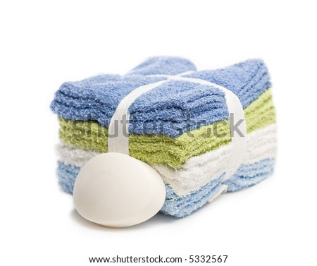 Stack of washcloths with bar of soap isolated on white - stock photo