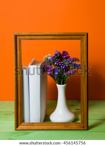 Stack of White books in brown wooden frame on an orange background on a green wooden table, pen, free copy space, vase with Flowers, no labels, blank spine. Back to school - stock photo