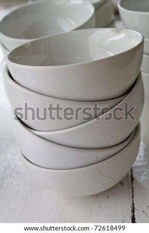 Stack of white bowls on the table wood.