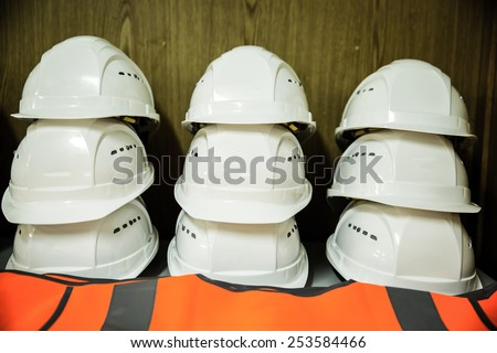 Stack of white construction workers' helmets with reflective protection clothes underneath - stock photo