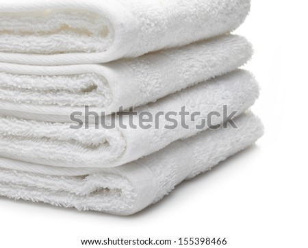 Stack of white hotel towels on a white background - stock photo