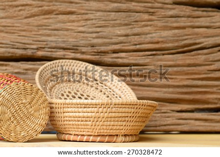 stack of wicker basket on old wooden table - stock photo