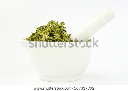 Stack of wild Thyme flowers and leaves in white porcelain mortar isolated on white background, side view - stock photo