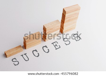 Stack of wood block in statistics graph shape with text SUCCESS. Business concept in rising and growing successful. Selective focus, gray background. - stock photo