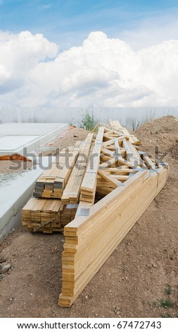 stack of wooden joists and building lumber at construction cite against a blue sky. - stock photo