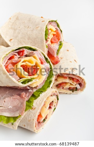 stack of wrapped tortilla sandwich rolls cut in half on white background - stock photo