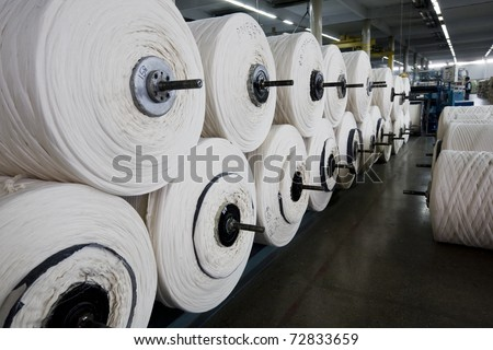 Stack of yarn spools in a textile mill. - stock photo