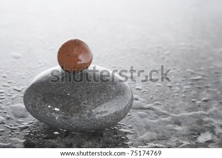 Stack of zen pebbles on a shiny, wet surface
