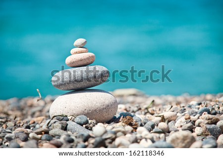 stack of zen stones over sea and blue background  - stock photo