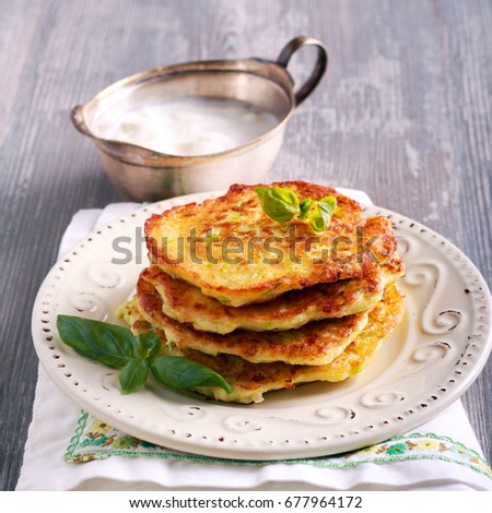 Stack of zucchini and feta fritters on plate, square image