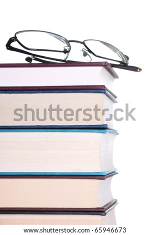 Stack or pile of old hardback books with reading glasses on a white background for copy space - stock photo