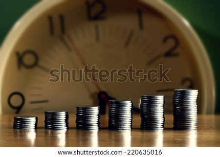 stack or piles of philippine peso coins and a clock - stock photo