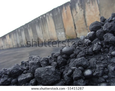 stack pile of charcoal coal on an industrial background - stock photo
