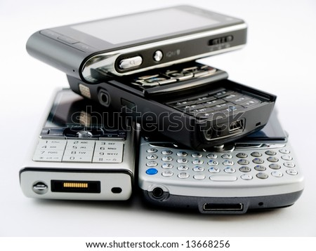 Stack Pile of Several Modern Mobile Phones PDA Cell Handheld Units Isolated on White Background - stock photo