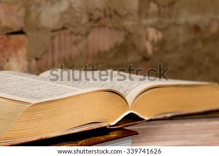 stack thick books on the table against a brick wall