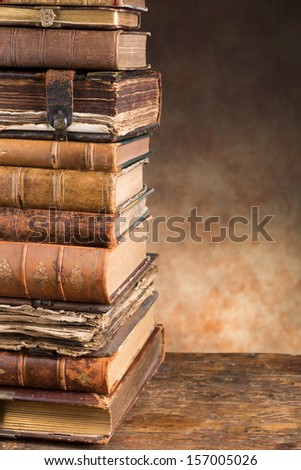 Stacked antique very old books leaving copy space - stock photo