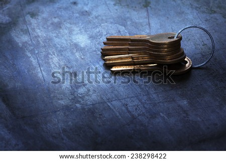 Stacked Brass keys on a bluish old metal background. - stock photo