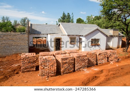 Stacked bricks in front of an incomplete house. - stock photo