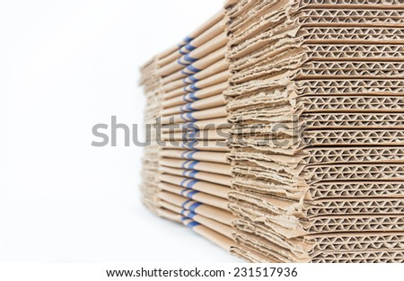 Stacked brown corrugated cardboard boxes isolated on white background with copy space. Side and edge perspective view of flattened boxes. Nice for new packaging or recycling idea.  - stock photo