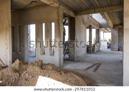 Stacked building material in the yard of a half completed concrete commercial building showing detail of the design with beams and supports - stock photo