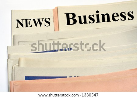 Stacked business newspapers on white background