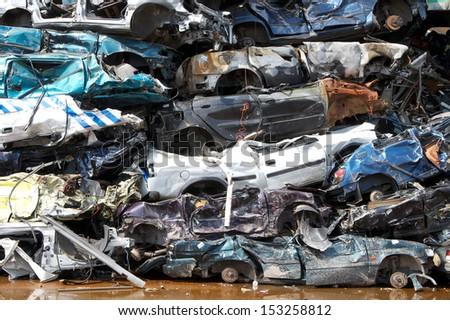 Stacked cars in junkyard - stock photo