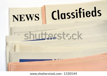 Stacked classifieds newspapers on white background