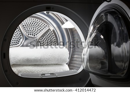 Stacked clean white towels inside washing machine drum. Clean concept. Laundry. Closeup of open washing machine.  - stock photo