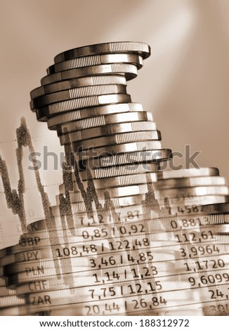 Stacked coins and currency rates - stock photo