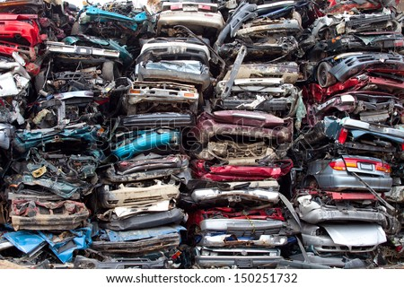 Stacked crushed cars going to be shredded in a recycling facility - stock photo