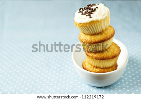 Stacked cupcakes in a bowl with frosting on top - stock photo