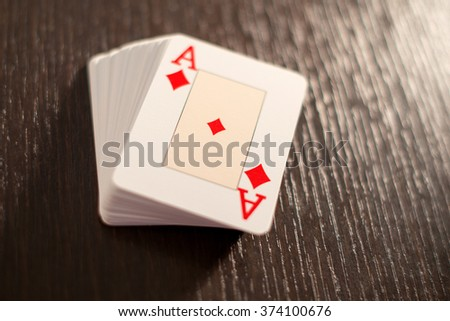 Stacked deck of playing cards showing the ace of diamonds on the top on a textured wooden table with back light and copy space