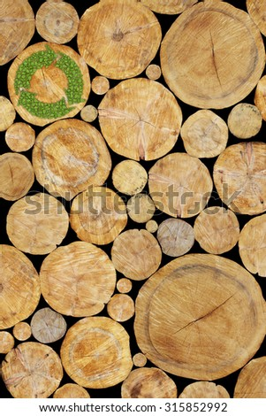 Stacked Logs with green plant recycle symbol, natural wood background - stock photo