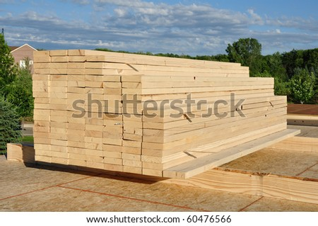 Stacked Lumber at Residential Home Construction Site - stock photo