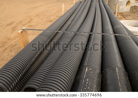 Stacked new PVC pipe on construction site - different focus