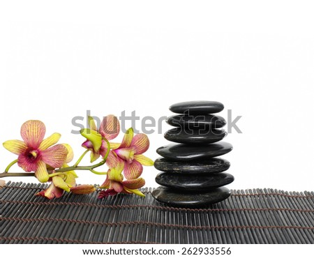 Stacked of black stones and branch orchid on bamboo mat - stock photo