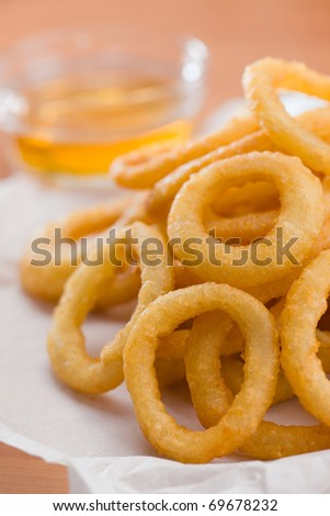 Stacked onion ring on a white waxed paper. Honey sauce  in the backgroundVery shallow depth of field. - stock photo